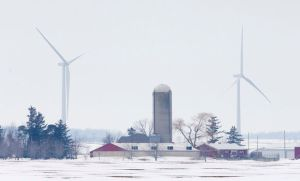 A farm stands in the foreground as some of the 45 wind turbines at the Bornish Wind Energy Centre stand in the distance near Parkhill. (Free Press file photo)