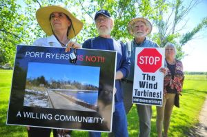 Port Ryerse residents protested as members of an environmental tribunal hearing into the case of wind turbines proposed for a field next to their village visited the site on Wednesday, June 3, 2015. From left to right are: Mary Goodlet, Bill Irvin, Stew Smith, and Shana Greatrix. (DANIEL R. PEARCE Simcoe Reformer)