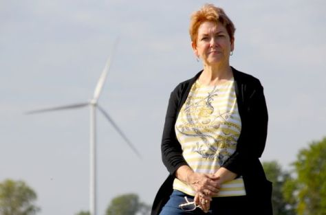 Betty Konc is pictured in Wainfleet with an industrial wind turbine behind her. (Greg Furminger/Welland Tribune/Postmedia Network)