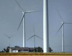 house surrounded by wind turbines